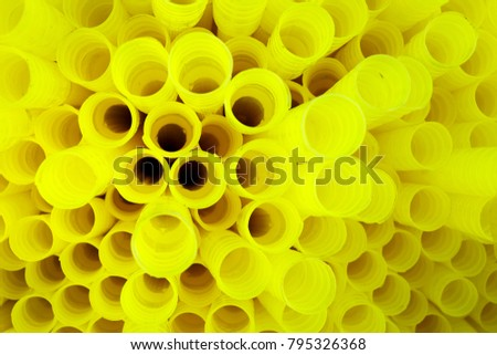 Detail of texture of yellow flexible plastic tubes stuffed together. The cylinders are components used in the production of explosives for the mining industry. #795326368