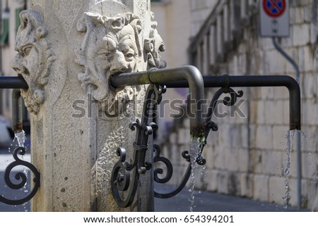 Detail of the ancient fountain in the town hall square in Venzone with goblins' heads on the four sides #654394201