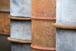 Detail of the curves of rusty metal barrels neatly lined up in alternating colors of warm rusty red and pale pastel blue