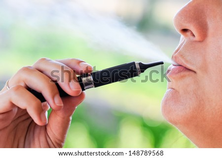 Detail of the electronic cigarette with its vapor similar to traditional cigarette smoke