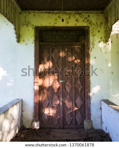 Detail of the entrance of an old colonial house, abandoned. Wooden door with carved details.  Shadow of the fig tree in front of the house. Rolante, Rio Grande do Sul, Brasi.