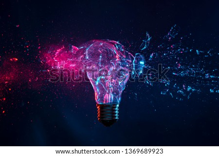 detail of the explosion of a filament light bulb, high speed photography. Studio shot with purple and blue artificial light on a dark background.