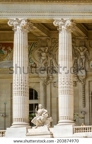 Detail of the facade of the Grand Palais, the corinthian columns a statue and the frescoes on the walls. Paris, France.