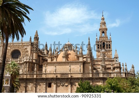Detail of the gothic and baroque Cathedral of Seville and the famous bell tower called La Giralda that was previously a minaret of the Berber Almohad period in Spain.