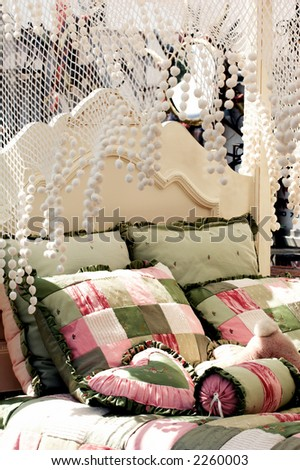Detail of the head board and canopy of a canopy bed at an outdoor flea market