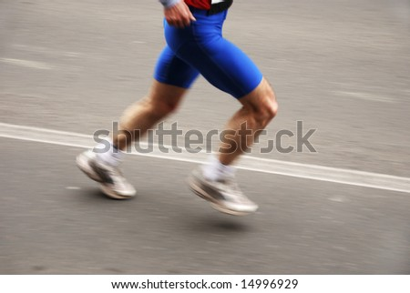 detail of the legs of a marathon runner with slight panning effect - stock photo
