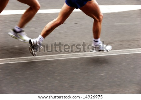 detail of the legs of two marathon runners with slight panning effect