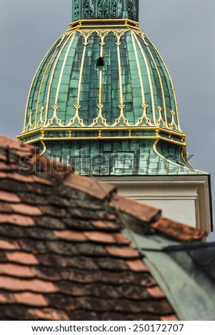 Detail of the main tower in Bratislava, Slovakia. Green roof with gold elements on a red tile roof
