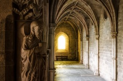 Detail of the medieval gothic cloisters of the cathedral of Evora, main city of the Alentejo region (Portugal) with an evangelist statue holding the bible