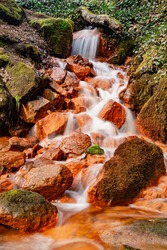 Detail of the mineral springs. Cascade on stream of mineral water with ferric sediment on green mossy boulders.