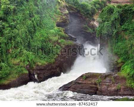 detail of the Murchison Falls with green overgrown rock formation in Uganda (Africa)