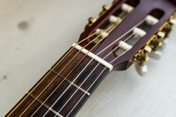 Detail of the neck and pegs of a Spanish guitar. Brown classical guitar with detail of guitar strings.