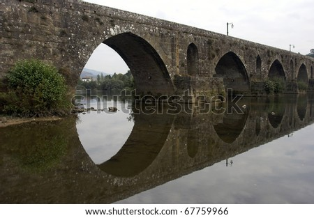 Detail of the old bridge of Ponte de Lima (north of Portugal) with reflection
