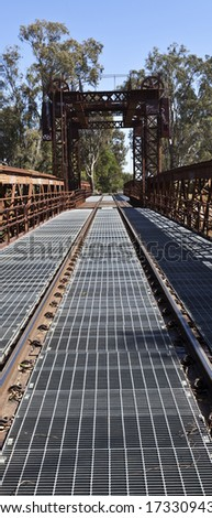 Detail of the railway track converging towards a vanishing point after the bridge end