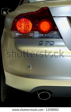 Detail of the rear end of a silver car with the brakelights blazing.
