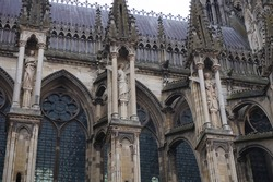 Detail of the side facade of the Gothic Cathedral of Notre-Dame de Reims, in France ; the stained glass windows feature fine stone tracery, while the flying buttresses are adorned with statues