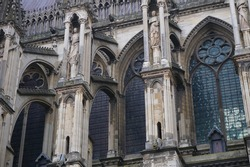 Detail of the side facade of the Gothic Cathedral of Notre-Dame de Reims, in the Northeast of France, featuring flying buttresses adorned with stone statues, and the upper stained glass windows