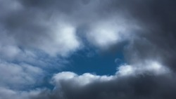 Detail of the sky on a rainy day. Dramatic clouds ranging from dark grey to white. In the middle of an open, you can see the blue sky, wrapped in a tear of light.