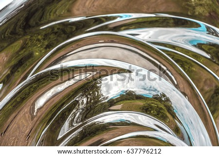Detail of the surface of metal sculpture. Beautiful abstract texture of the metal construction as background for design. Trees reflected in modern art object. Full frame. Curved distorted reflections. #637796212