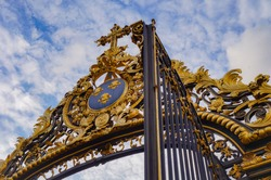 Detail of the 18th century gilded gate of the Hôtel-Dieu-le-Comte, a townhouse built in the 12th century in Troyes, France ; the golden heraldry, featuring the Regal Lily,  is topped by a cross