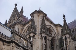 Detail of the transept, adorned with stone pinnacles, and of the side facade of the Gothic Cathedral of Notre-Dame de Reims, in the Northeast of France ; the roofs are topped with fleur-de-lys