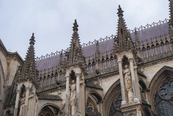 Detail of the upper part of the side facade of the Gothic Cathedral of Notre-Dame de Reims, in France, featuring flying buttresses topped with pinnacles, and the roof, adorned with fleur-de-lys