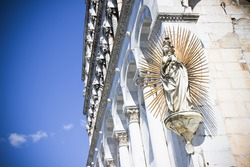 Detail of the Virgin Mary sculpture with Jesus on the corner of the facade of Saint Michael church (Italy-Tuscany-Lucca)