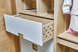 Detail of the wardrobe close-up. Modern wardrobe with opened wooden drawers. Wooden wardrobe with flat finger pull wardrobe doors. Oak veneered plywood cabinets with light gray painted cabinet doors