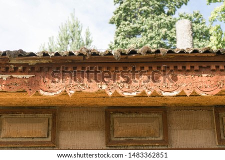Detail of the wooden building. Old house with wood lace under the roof. Orange color is peeling off from fine details. Moss and lichen hanging from the roof. Aegviidu, Estonia