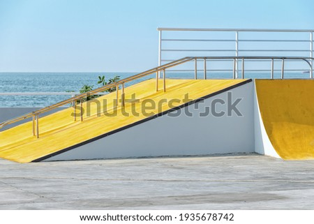 Detail of the yellow ramp skating park with blue sky and grey concrete. Bright architectural element Stockfoto ©