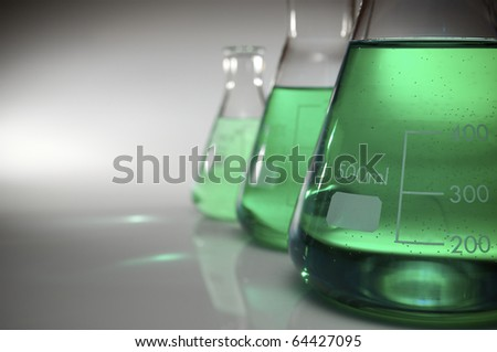 detail of three flasks containing green liquid