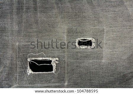 Detail of torn Black denim, front view  jean  background or texture