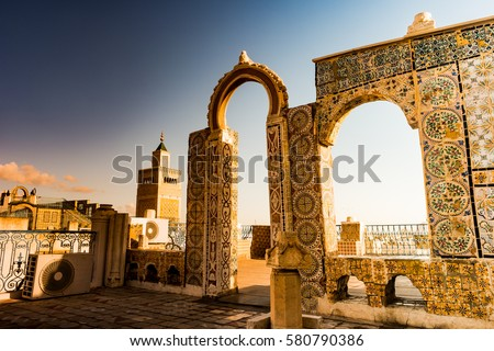 Detail of traditional arabic architecture in cityscape at dawn with dramatic sunlight. Tunisia, North africa.