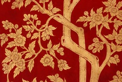 Detail of traditional red painting depicting trees and leaves on a door at the the Wat Phra Kaew Palace, also known as the Emerald Buddha Temple. Bangkok, Thailand.