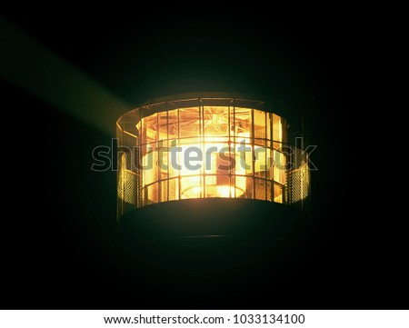 Detail of turning lamp in lighthouse. Detail of Fresnel lens. Tower illuminated with strong warning light. Shinning old lighthouse with dark night. Lighthouse in Prerow, Germany
