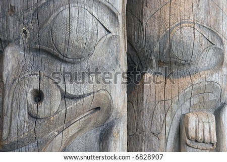 Detail of two faces on a pair of old, worn, unpainted, wooden West Coast Indian totem poles in a Vancouver, British Columbia park.