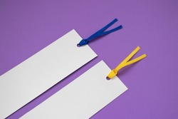Detail of two paper bookmarks on a purple background