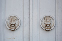 Detail of two white antique tiger or lion bas relief sculptures and metal door knocker's rings on wooden white door.