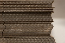 Detail of uneven stack of corrugated cardboard sheets with soft focus background