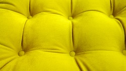 Detail of upholstery of modern sofa, chair, armchair, pouf or pillow. Carriage coupler. Yellow color. Premium luxury fabric. Cozy home. Design interior. Cushions decor. Furniture manufacture. Summer