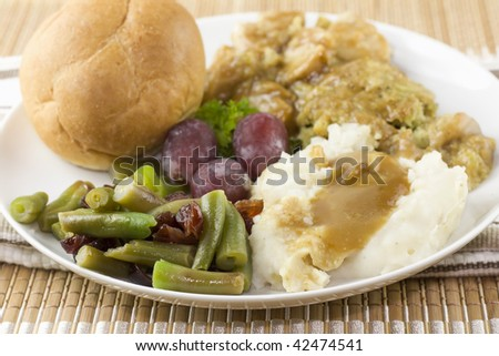 detail of vegetable portion of a turkey dinner including mashed potatoes and cranberry accented green beans