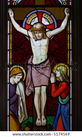 detail of victorian stained glass church window in Fringford depicting Jesus nailed to the cross with St. Mary and St. John at the feet of the cross