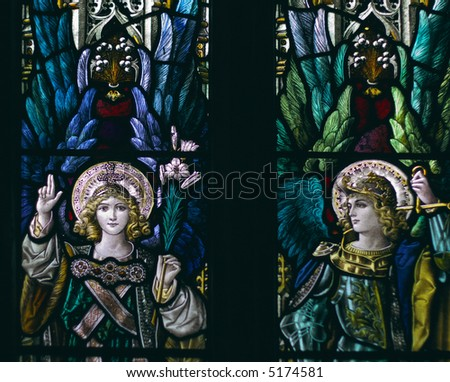 detail of victorian stained glass church window in Fringford depicting two typical victorian angels with a sword and a lily in their hands