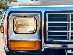 Detail of vintage car, frontal view. Headlight, turning light and chrome grill of historic american SUV. American memorabilia and car collectors.