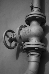 Detail of vintage valves, tubes and pipes with big metal cranks and metal rivets and studs, black and white photo, concept of vintage industrial