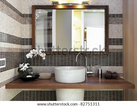 detail of washbasin in modern bathroom with a vase of white orchid