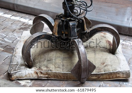 Detail of waste plant: Old mattress with large claw on conveyor belt