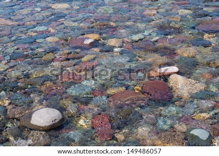 Detail of water flowing over colorful rocks.