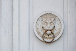 Detail of white antique tiger or lion bas relief sculpture and metal door knocker's ring on wooden white door.