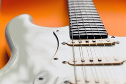 Detail of White Electric Guitar on a orange background.